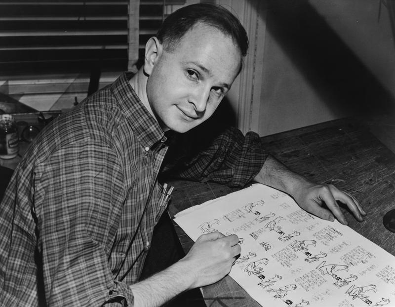 Jules Feiffer, American cartoonist, seated at work on cartoon.