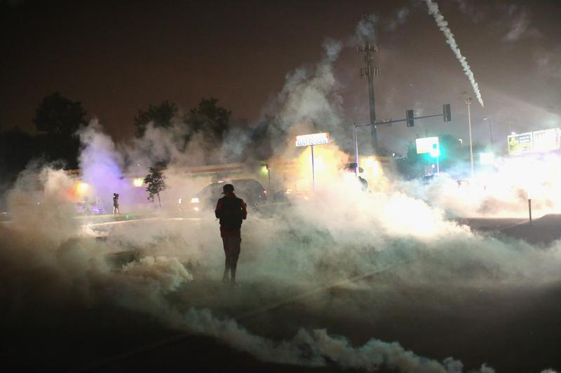 A person runs through a clowd of tear gas that police launched at demonstrators protesting the killing of teenager Michael Brown on August 17, 2014 in Ferguson, Missouri.