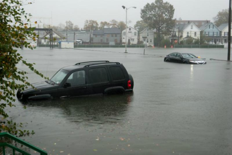 A car in a flooded parking lot.