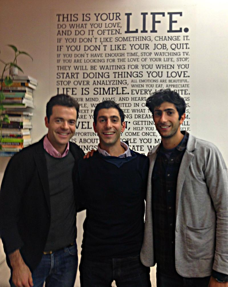 Holstee co-founders Fabian Pfortmüller, Michael Radparvar and Dave Radparvar in front of the Holstee Manifesto, a poster of motivational sayings that's popular in the tech sector.