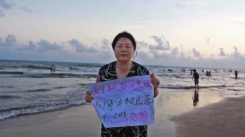 Chinese activist Ye Haiyan (aka Hooligan Sparrow) holds a sign that criticizes the lack of women's rights in China.