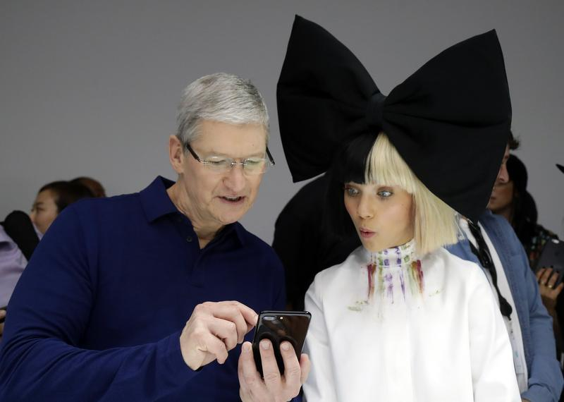 Apple CEO Tim Cook shows an iPhone 7 to performer Maddie Ziegler during an event to announce new products, Wednesday, Sept. 7, 2016, in San Francisco.
