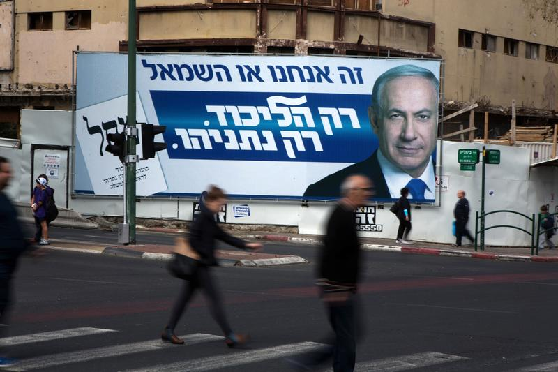 Israelis walk past by campaign posters showing Israeli Prime Minister and Likud party's candidate running for general elections, Benjamin Netanyahu on March 12, 2015.
