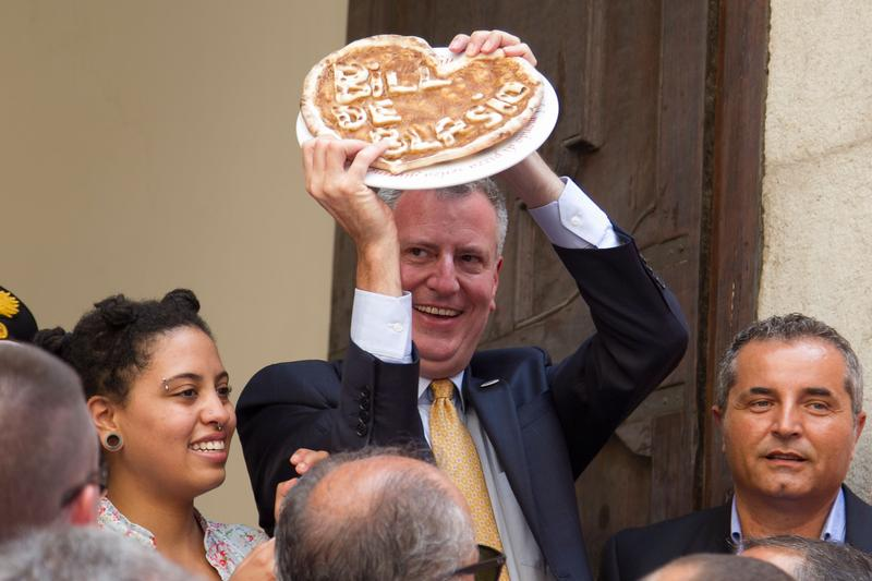 New York City mayor Bill De Blasio and his family holds a pizza with his name on it as he visits the town, Sant'Agata de' Goti, Italy, his grandfather Giovanni de Blasio was born in.