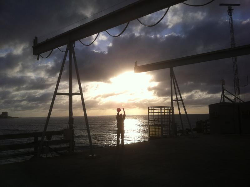 Scripps technician Kim Bracchi is silhouetted in a setting sun as she collects air in a flask for CO2 analysis.