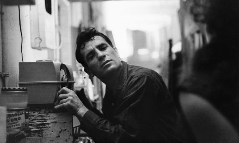 Jack Kerouac leans closer to a radio to hear himself on a broadcast, 1959