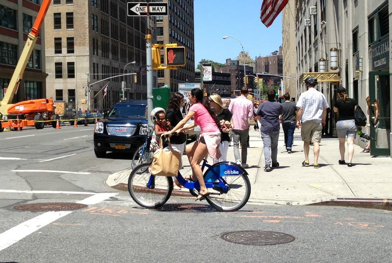 A Citi Bike user, illegally toting a child in the front basket