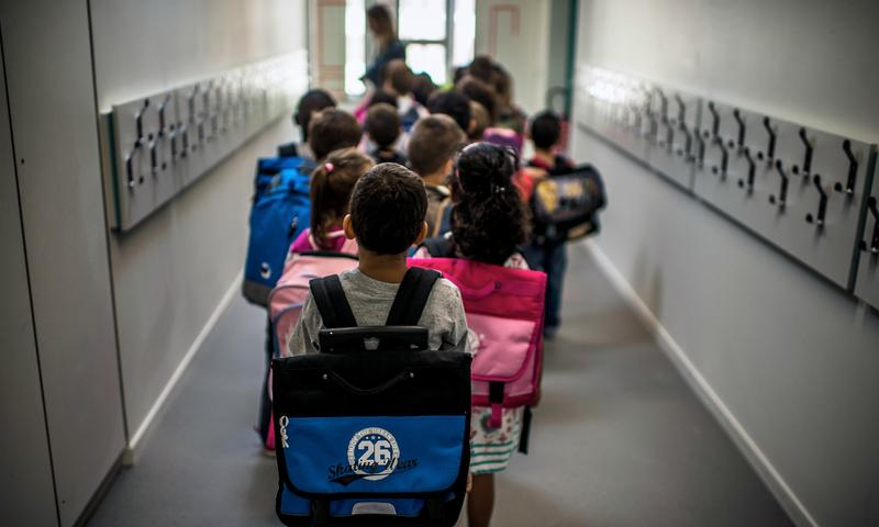 Children wait in line to go to class on the first day of school