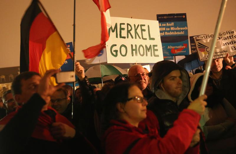 Supporters of the AfD political party protest against German Chancellor Angela Merkel's liberal policy towards taking in migrants and refugees on October 14, 2015 in Magdeburg, Germany.