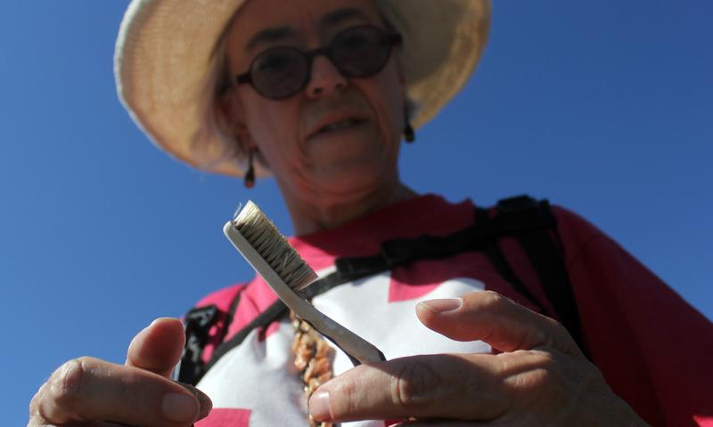 Artist Deborah McCullough holds a toothbrush found along the US-Mexico border. Discarded toothbrushes are a common in the desert; McCullough uses them as material in her art installations.