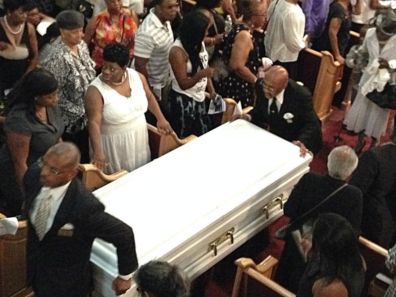 Pallbearers move the white casket of Eric Garner out of the church.