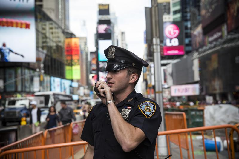 A New York City police officer speaks on his radio in Times Square.