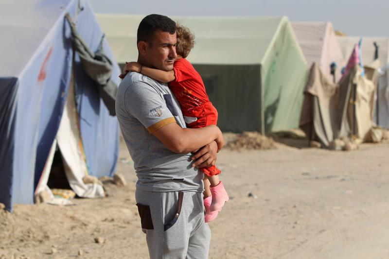 A displaced Iraqi man, who fled Ramadi, the capital of Anbar province, after it was seized by the Islamic State (IS) group, holds a child at a makeshift camp for internally displaced persons (IDP).
