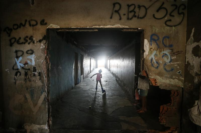 A young resident rollerblades in an occupied building in the Mangueira 'favela' community on July 12, 2016 in Rio de Janeiro, Brazil.