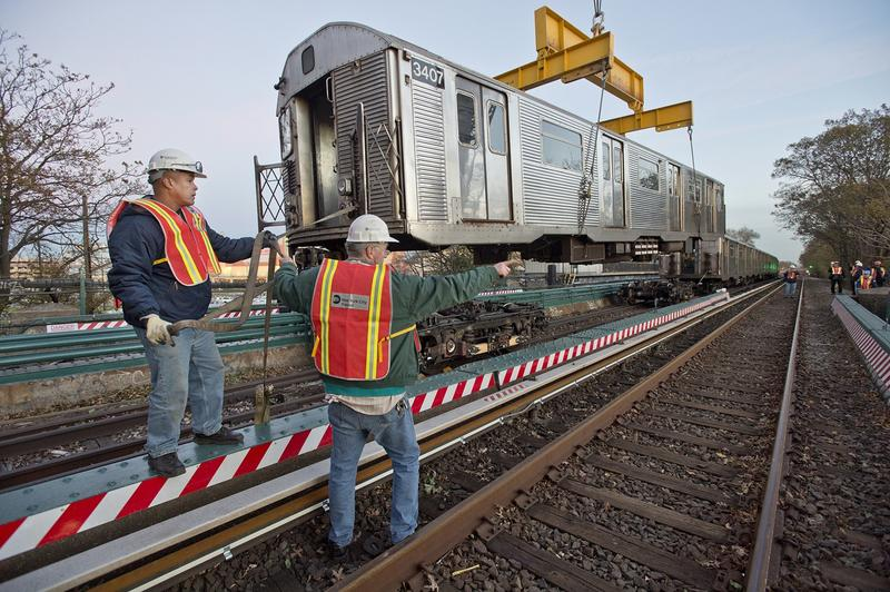 NYC Transit employees loading subway cars onto flatbed trucks for transportation to the Rockaway Peninsula in November, 2012