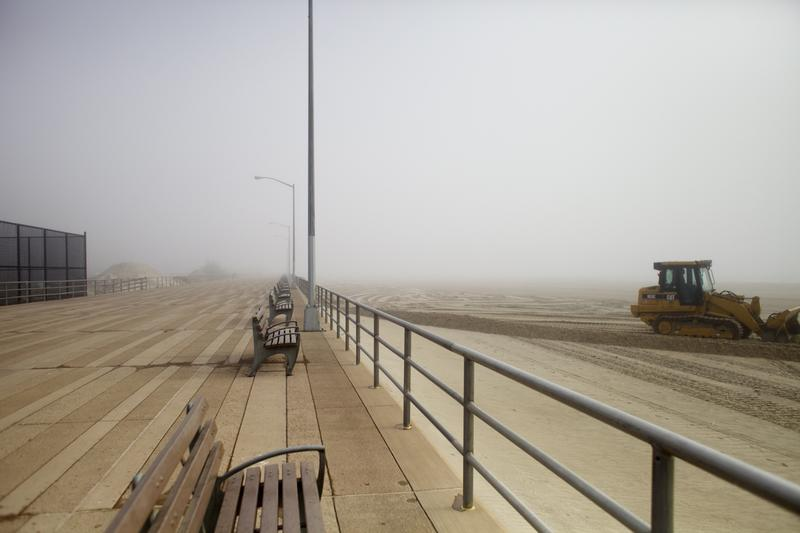 The boardwalk stretches off into the fog at Beach 81st Street in The Rockaways as a bulldozer spreads sand.