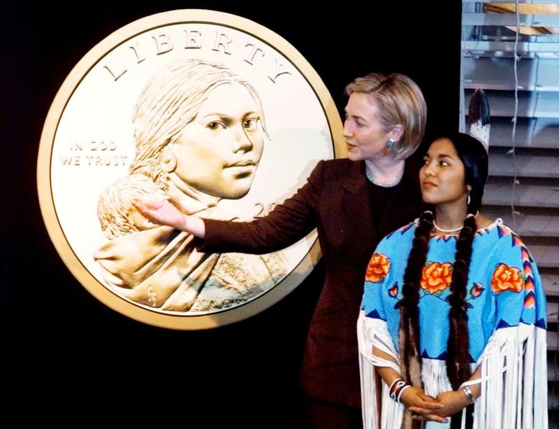 First Lady Hillary Rodham Clinton, accompanied by Randy Teton, who modeled for the Sacagawea dollar coin, points to an enlarged version of the coin during an introduction ceremony in 1999.