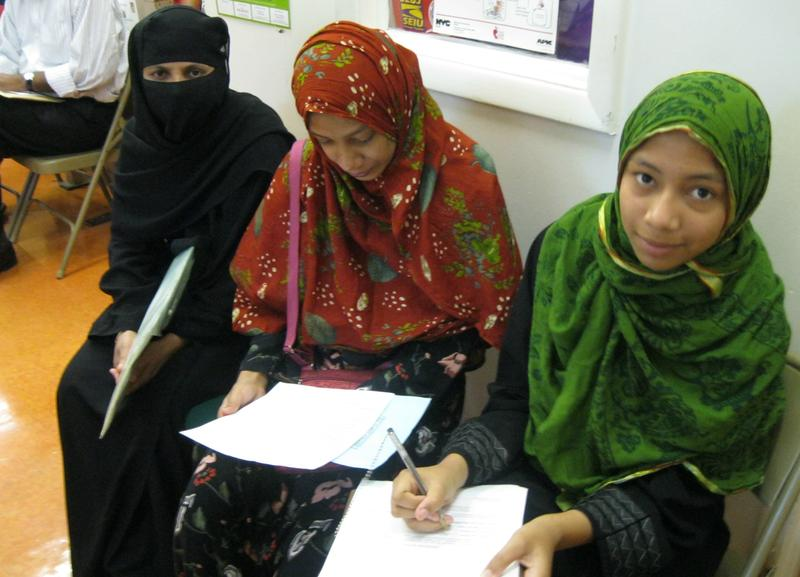 Habiba Riva, center, gets help filling out enrollment paperwork from her sister Kulsum, who is fluent in English.