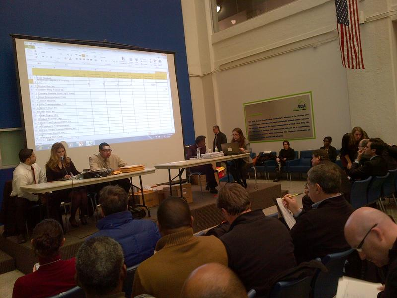 School bus industry representatives took notes as bids were opened for 1100 routes at the School Construction Authority's office in Queens.