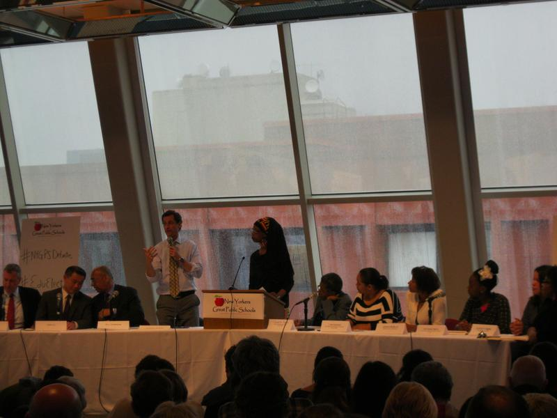 Anthony Weiner, standing, during a Democratic candidates debate on education moderated by  parent leader Zakiyah Ansari (to right of Weiner)