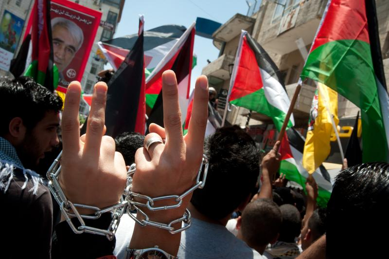 Palestinians marching in Ramallah wear chains around their wrists to symbolize their solidarity with prisoners incarcerated by Israel, May 15, 2012.
