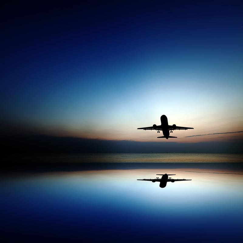 A plane flies over a body of water at sunset.