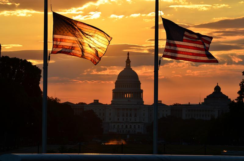 United States Capitol building silhouette and US flags at sunrise.