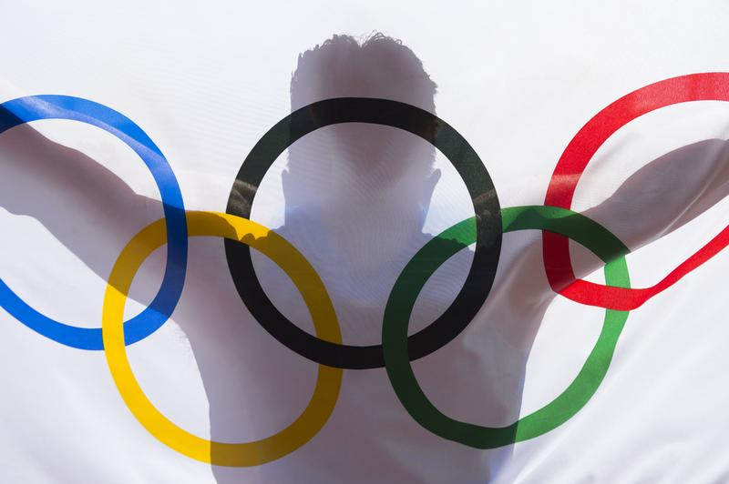 RIO DE JANEIRO - FEBRUARY 3, 2016: Shadow silhouette of athlete holding an Olympic flag in anticipation of the 2016 Summer Games.