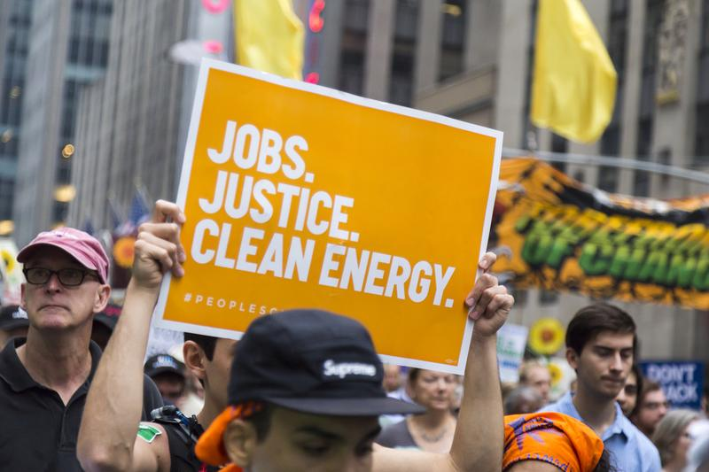 Person carries a placard supporting 'Jobs, Justice, Clean Energy' and demonstrates for environmental awareness during the 2014 People's Climate March, New York, USA