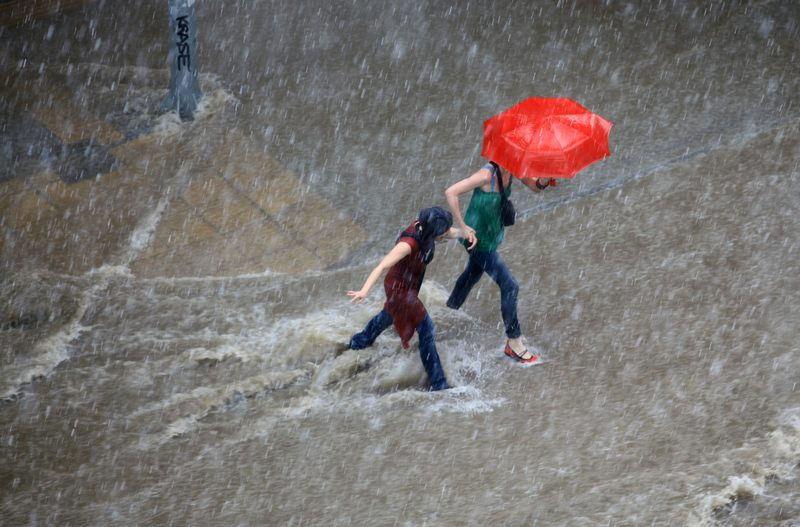 People try to cross a flooded road in the center of city on June 15, 2011 in Macedonia, Thessaloniki, Greece.