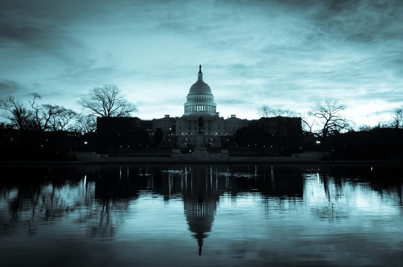 Washington D.C. Capitol building in a cloudy sunrise with mirror reflection.