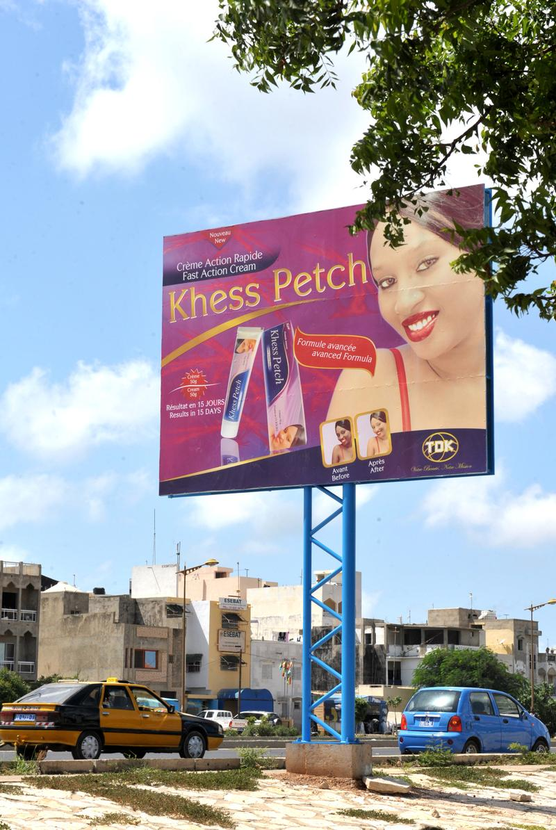 Cars pass by a billboard advertising a skin lightening product called 'Khess Petch' on October 10, 2012 in Dakar.