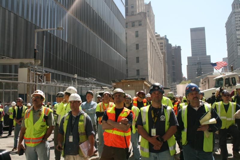 Construction workers watch as a 408-foot spire is hoisted onto One World Trade Center.