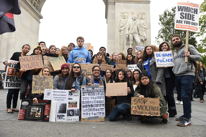 College students pose with signs in front of Washington Square arch prior to marching on October 24th, 2015.
