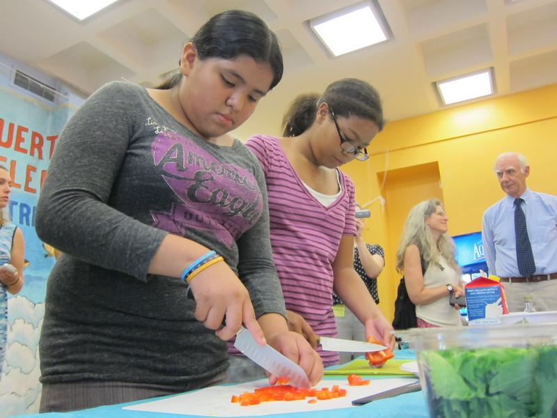 Two students chop vegetables to be used in omelets in a cooking class meant to teach students math and nutrition.