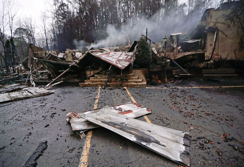 Smoke rises from the remains of the Alamo Steak House on Nov. 30, 2016, in Gatlinburg, Tenn., after a wildfire swept through the area.