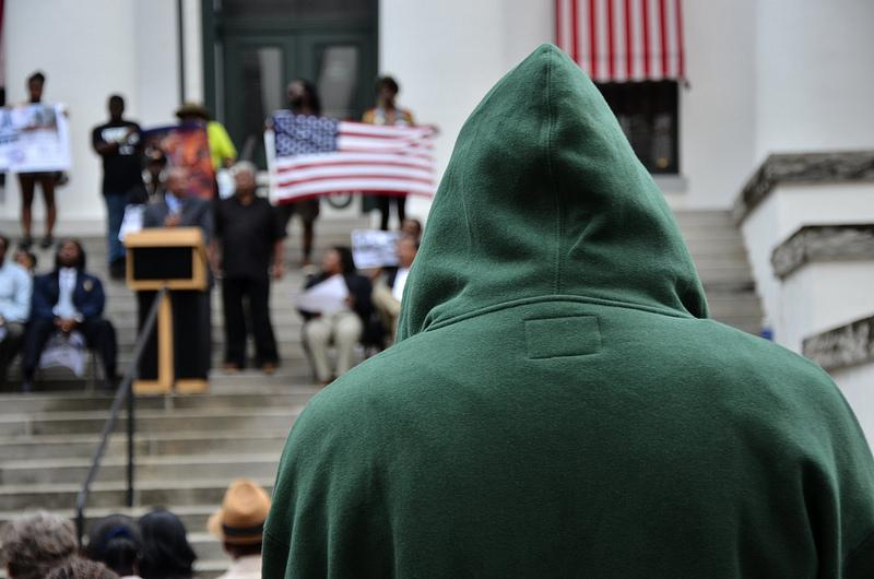 A man with hoodie watches the speakers on the steps of the Capitol Building in Tallahassee, Florida at a Rally March for Trayvon Martin.