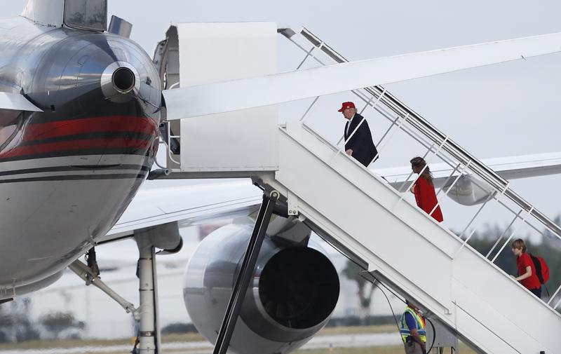President-elect Donald Trump, followed by his wife Melania Trump and son Barron Trump, boards his plane at Palm Beach International Airport, Sunday, Nov. 27, 2016.