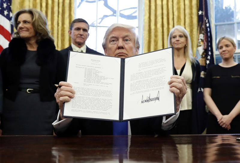 President Donald Trump holds up a signed Presidential Memorandum banning travelers from seven Muslim-majority nations.