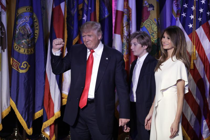 President-elect Donald Trump pumps his fist after giving his acceptance speech as his wife Melania Trump, right, and their son Barron Trump follow him during his election night rally.