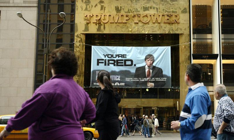 """Passersby look at a sign from """"The Apprentice"""" hung on the Trump Tower in New York"""