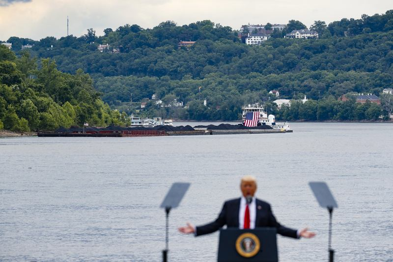 A coal barge is positioned as a backdrop behind President Donald Trump as he speaks about infrastructure during a rally at the Rivertowne Marina, Wednesday, June 7, 2017, in Cincinnati.