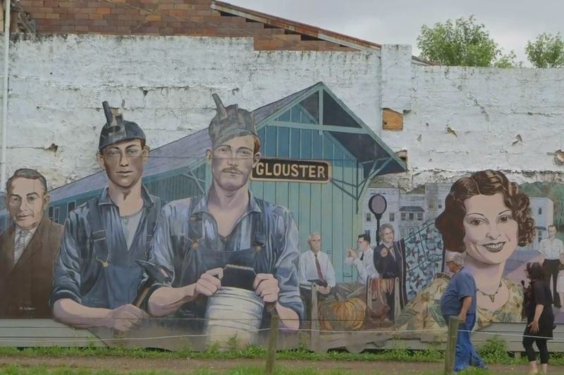 Brooke Gladstone and Jack Frech in front of a mural in Glouster, Athens County, Ohio.