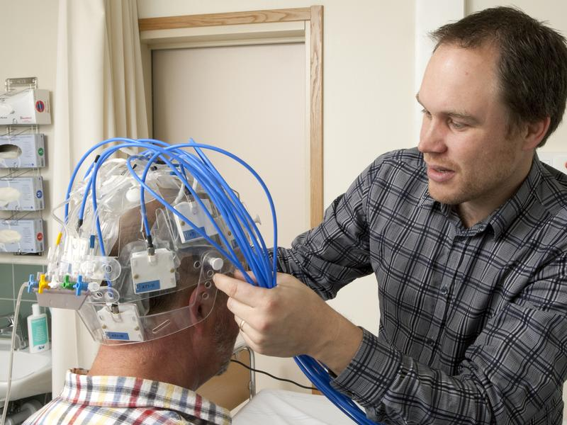 Andreas Fhager, a biomedical engineer at the Chalmers University of Technology in Sweden, adjusts the Strokefinder device on a test subject's head.