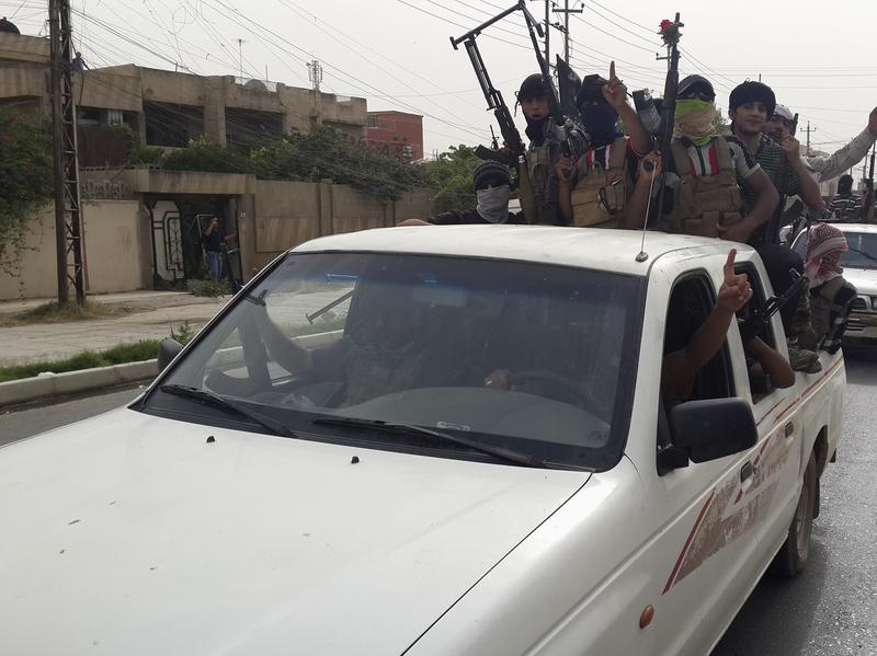 Fighters of the Islamic State of Iraq and Syria celebrate on vehicles taken from Iraqi security forces in Mosul, Iraq, on Thursday.