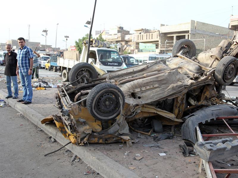 Iraqis inspect destruction in the street following an explosion in Sadr City, Baghdad's northern Shiite-majority district in May.