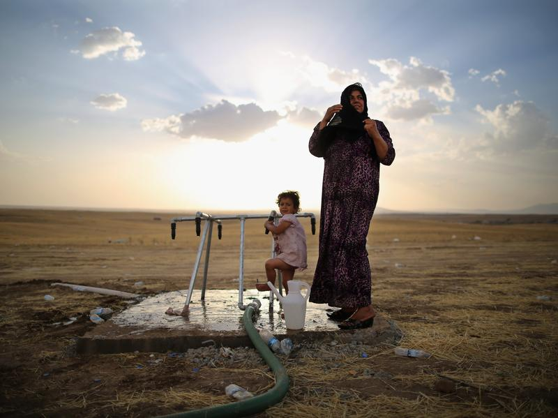 A woman and a girl wash at a camp in Kalak set up for those fleeing the fighting in northern Iraq. The escalating conflict has sent shock waves across the region and is further destabilizing the Middle East.