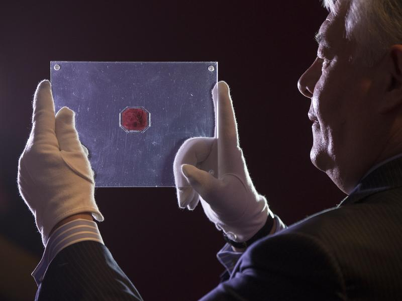 "David Redden of Sotheby's auction house holds a case containing the sole surviving ""British Guiana One-Cent Black on Magenta"" stamp dating from 1856."