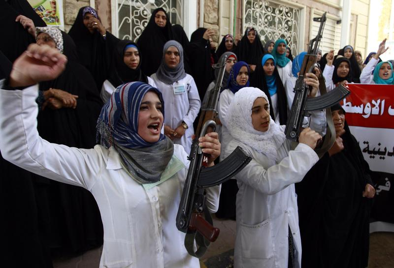 "Iraqi Shiite women hold their weapons as they gather to show their willingness to join Iraqi security forces in the fight against Jihadist militants who have taken over several northern Iraqi cities, on June 18, 2014 in the southern Shiite Muslim shrine city of Najaf. Iraq's premier vowed today to ""face terrorism"" and insisted security forces had suffered a ""setback"" rather than defeat, as militants pressing a major offensive attacked the country's largest oil refinery. (Haidar Hamdani/AFP/Getty Images)"