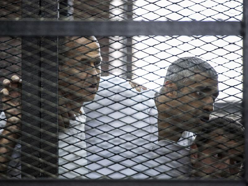 Australian journalist Peter Greste (left) of Al-Jazeera news channel and his colleagues, Egyptian-Canadian Mohamed Fadel Fahmy (center) and Egyptian Baher Mohamed, listen to the verdict inside the defendants' cage during their trial for allegedly supporting the Muslim Brotherhood.
